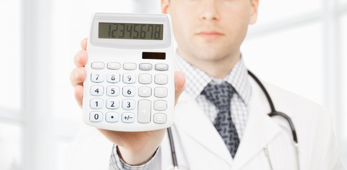 Medical doctor with a calculator in his righ hand showing calculated costs and revenues in physician practice and hospital fees