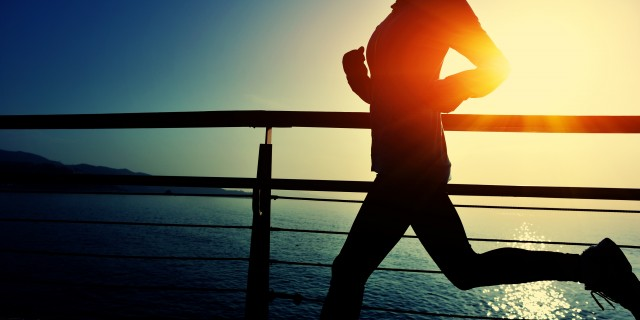 young fitness woman running on sunrise seaside boardwalk