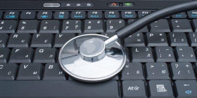 Medical stethoscope laying on a computer keyboard